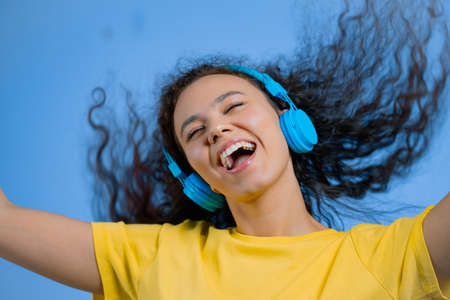 Attractive woman dancing with wireless headphones on blue studio background. Cute girl dancing and smiling. Music, radio, happiness, freedom, youth concept.