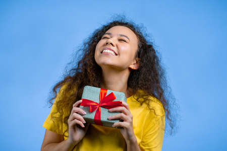 Beautiful woman received gift box with bow. She is happy and flattered by attention. Girl smiling with present on blue background. Studio portrait