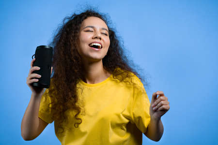 Mixed race woman listening to music by wireless portable speaker - modern sound system. Teenager dancing, enjoying on blue studio background. She moves to the rhythm of music.
