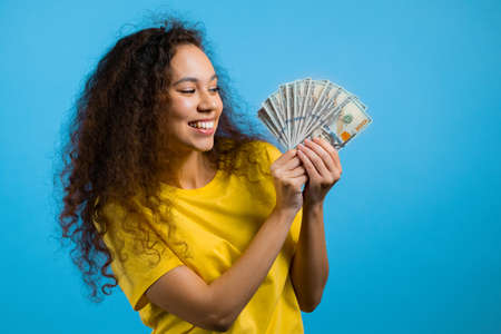 Smiling happy woman with cash money - USD currency dollars banknotes on blue wall. Symbol of jackpot, gain, victory, winning the lottery