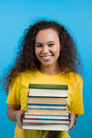 Student girl holds stack of university books from library on blue background in studio. Woman smiles, she is happy to graduate.