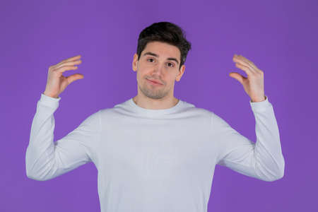 Handsome bored man showing bla-bla-bla gesture with hands and rolling eyes isolated on violet background. Empty promises, blah concept. Lier