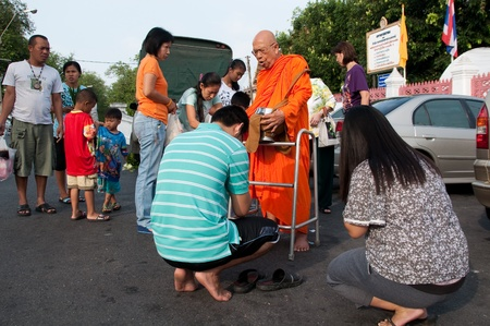 Wat Benchamabophit, Bangkok, Thailand - May 17, 2011 - Thai people give alms to a old Buddhist monk in front of Wat Benchamabophit on Visakha Bucha day