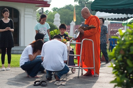 Wat Benchamabophit, Bangkok, Thailand - May 17, 2011 - Thai people give alms to a old Buddhist monk at  Wat Benchamabophit on Visakha Bucha day Stock Photo - 9538723