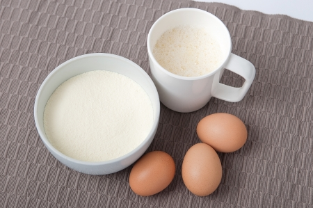 albumin: Dried albumin,eggs and dissolved albumin in white cup on talbecloth  Stock Photo