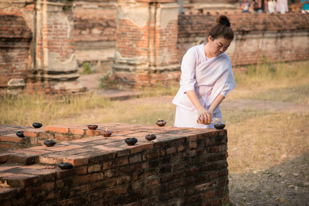 candlelit: WatMahaeyong, Ayutthaya, Thailand - February 22,2016 - Buddhist pour oil into lamp to prepare candlelit procession in Magha Puja Day.