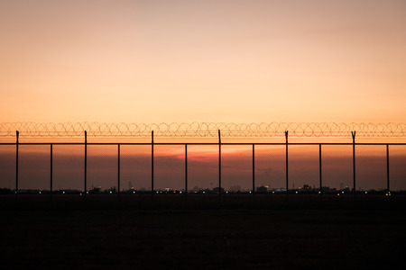 barbed wire frame: Silhouette barbed wire fence with dawn background