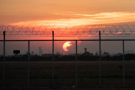 barbed wire frame: Sunset behind blurry fence with cloudy red sky Stock Photo