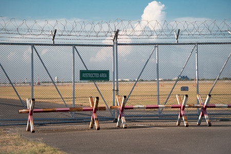 intrude: Barbed wire fence with green restricted area sign in the airport