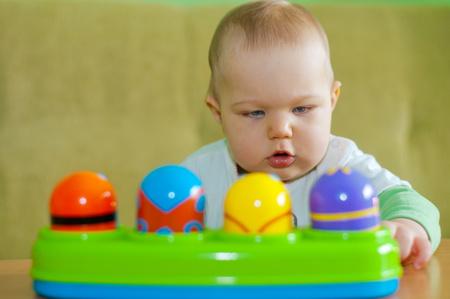 작은 아기가 그녀의 장난감으로 놀아 라.