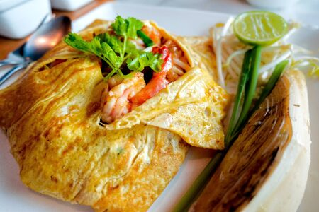 pad Thai (Fried Thai Noodle with Shrimp Wrapped in Egg) This menu, who comes to Thailand, must be tasted and then will be attracted. Stock Photo