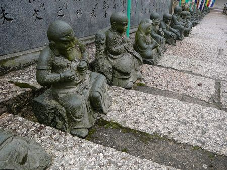 rain japan: Small statues on the stairs of a buddhist temple in Miyajima, Japan. I believe they depict deceased monks, the names written behind the statues.