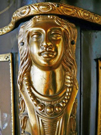 This womans head is on the edge of an old cabinet. Furniture this style was made be Boulle, the carpenter of the French king Louis XIV around 1700. Stock Photo