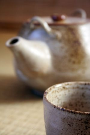 Teacup in the foreground and teapot in the background. Focus is on the cup. The style of cup and teapot is traditional Japanese pottery, similiar to the type found in Bizen.