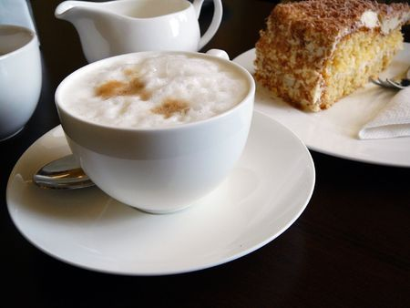afternoon fancy cake: cappuccino and a fancy cake on a dark wooden table. in germany, this type of meal is often enjoyed in the afternoon, about 4 oclock.