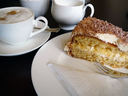 Fancy cake with a cup of cappucino, as served in a cafe in Europe.