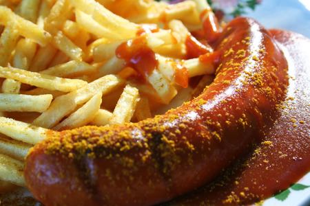 Currywurst, a fried sausage served with tomato ketchup and curry with fries. A typical snack in Berlin.  Stock Photo