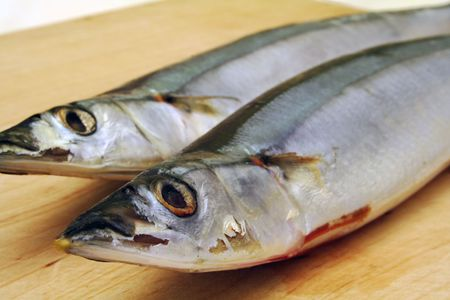 fish type: Fish ready to be fried or cooked on a wooden tray. It is a type of mackerel.  Stock Photo