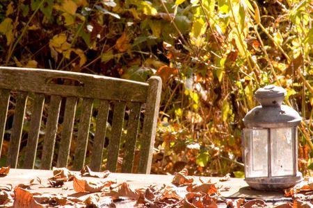 silla de madera: Una todav�a en el oto�o de la vida: una silla de madera, una mesa y una l�mpara en el jard�n.