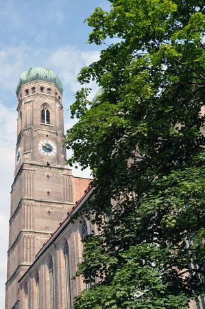 One of the mighty towers of Frauenkirche cathedral, partially hidden behind a tree.  Reklamní fotografie