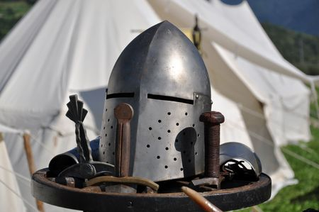 A helmet as worn by a medieval knight in middle Europe. Medieval-style tent in the background.  Stock Photo