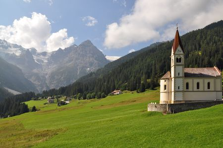 utilization: Alpine landscape formed by centuries of human utilization with farms houses, pastures and a church Stock Photo