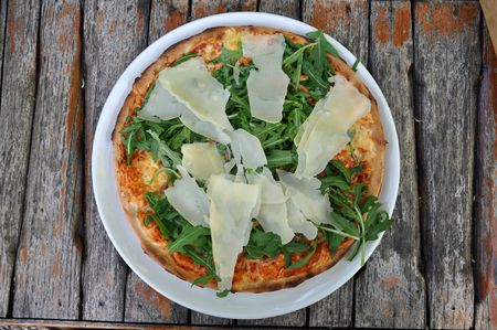 A tasty pizza covered with green rucola leaves and slices of parmigiano cheese.
