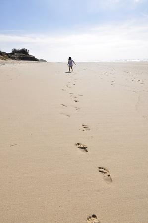 Een klein meisje draait weg op een brede, lege strand, voet afdrukken verlaten.