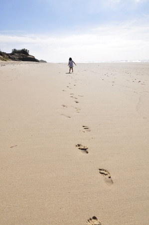 A little girl is running away on a wide, empty beach, leaving footprints.
