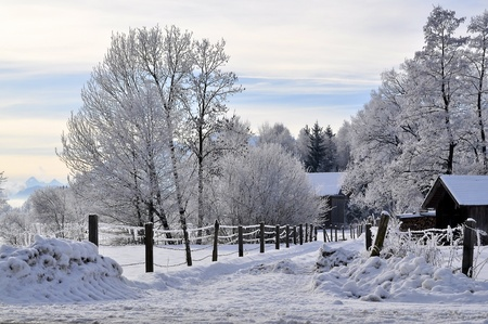 Winter landscape with a narro road leading to a small farm in Bavaria, Germany.