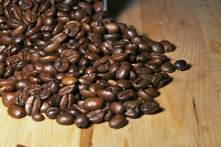 Coffee beans being poured from a metal tin.
