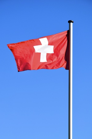 Flag of switzerland waving in front of a blue sky Stock Photo