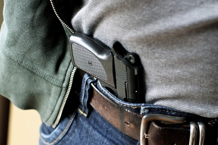 gun: Tucked in a belt pistol being concealed