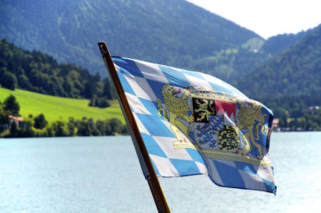 Flag of the state of Bavaria, Germany, waving over an alpine lake