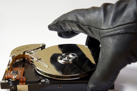 Depiction of the concept of data theft, opened harddisk and gloved hand, stealing information