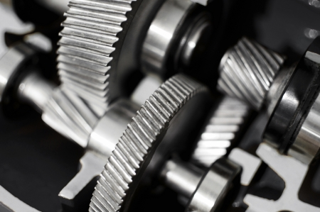 Closeup of a steel gearbox with many cogwheels