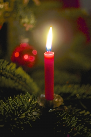 Burning, red candle on the Christmas tree  Christmas Bauble in the background   Stock Photo - 17207274