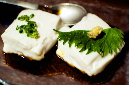 soysauce: Two small pieces of soft Japanese Tofu decorated with a leaf of Shiso and Ginger
