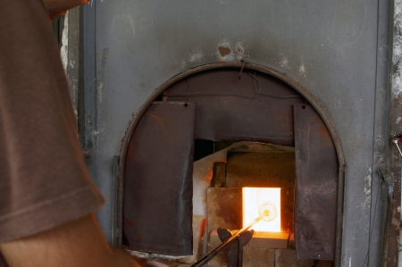 glassblower: Glass being melted by a gloss blower in a glass maunfacture