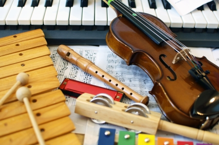 Musical instruments for children: xylophone, childrens violin, tambourine, flute, harmonica, piano keyboard.