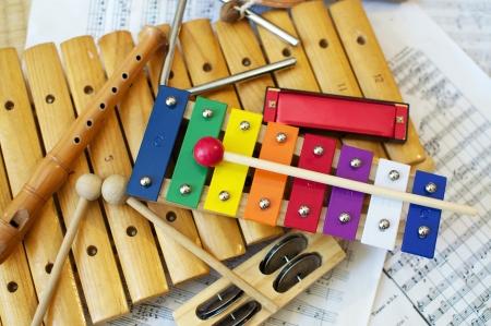 instrumentos musicales: Algunos instrumentos t�picos, colores musicales que se utilizan en su mayor�a por ni�os. La partitura musical en el fondo es de dominio p�blico. Foto de archivo