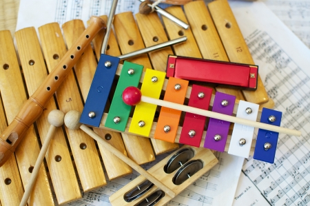 Enkele typische, kleurrijke muziek instrumenten zoals meestal gebruikt door kinderen. De muzikale score op de achtergrond is in het publieke domein.