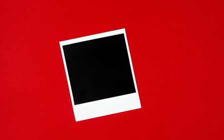 Original empty white black frame lying on a red background. Photo frame.