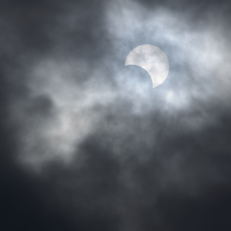 rifts: Partial solar eclipse seen and lost in the rifts of a hurrying sky.May,21,2012, Japan