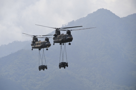 車を運ぶ 2 つのチヌーク ヘリコプター