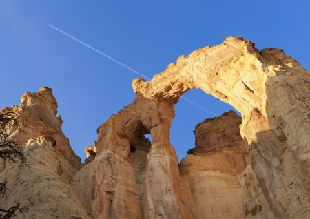 Grosvenor Arch against blue sky with contrail, Grand Staircase-Escalante National Monument photo