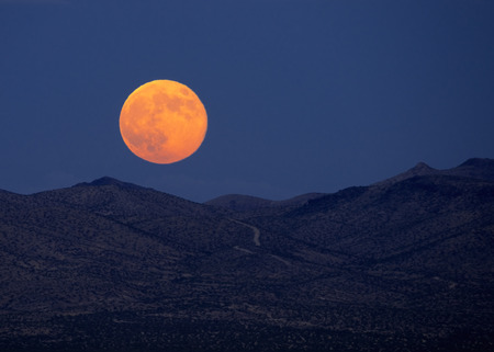 barstow: Supermoon rising over desert mountains