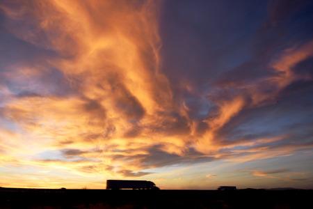 夕暮れ時に劇的な空の下で高速道路上のトラック。
