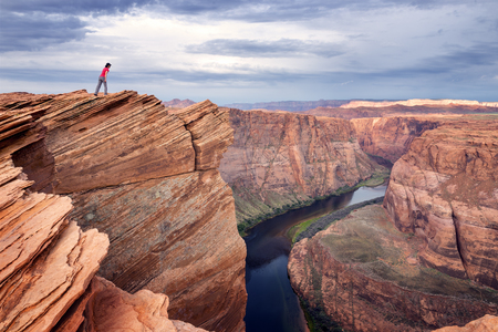 colorado river: A female hiker at the edge of cliff looking down at the Colorado river.