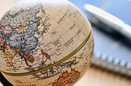 Globe Oost-Azië (balpen en notebook). Een wereldbol is photoed door close-up.